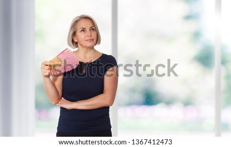 Attractive middle aged woman relaxing with fan. Mature woman experiencing hot flush from menopause isolated Royalty-Free Stock Photo #1367412473