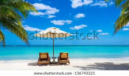 turquoise sea, deckchairs, white sand and palms, sun, very beautiful nature Royalty-Free Stock Photo #136743221