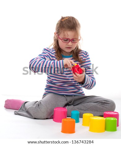 Little girl is playing with colorful building bricks #136743284