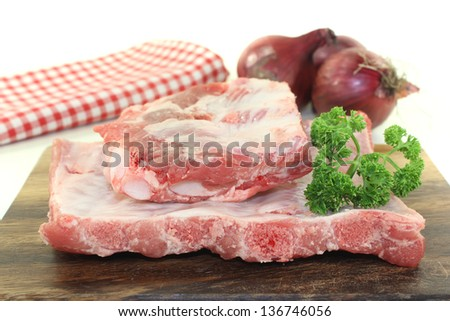 Beef spare ribs with parsley and onions on a wooden board in front of light background #136746056