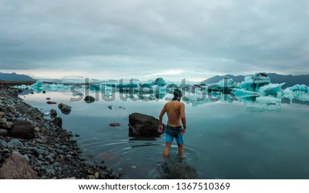 Young man enters the icy cold waters of Glacier lagoon. Man wearing only swimming shorts. Ice bergs drifting in the lagoon. Cold temperatures for ice swimming. Calm surface of the water #1367510369