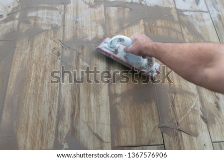 Grouting ceramic tiles. Tilers filling the space between tiles using a rubber trowel #1367576906
