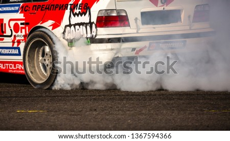 Shymkent / Kazakhstan - October 23, 2018: Demonstration performances cars for drifting on the city streets. Driving ride with drift. Smoke and dust from under the wheels of cars. #1367594366