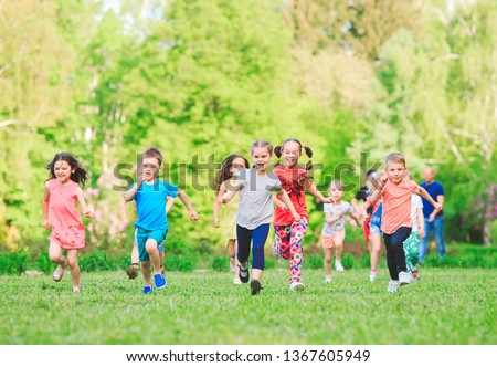Many different kids, boys and girls running in the park on sunny summer day in casual clothes #1367605949