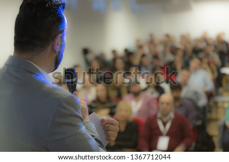 Young businessman at business conference room with public giving presentations. Audience at the conference hall. Entrepreneurship club. #1367712044