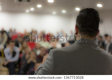 Young businessman at business conference room with public giving presentations. Audience at the conference hall. Entrepreneurship club. #1367713028