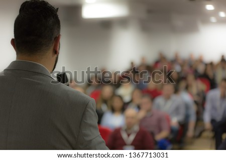 Young businessman at business conference room with public giving presentations. Audience at the conference hall. Entrepreneurship club. #1367713031