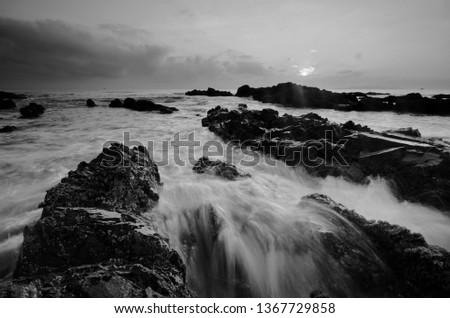Amazing rock formations at Pandak beach, Terengganu in black and white monochrome fine art technique.  Nature composition blur soft focus noise visible due to long exposure effect.