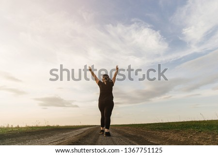 Body positive, freedom, high self esteem, confidence, happiness, inspiration, success, positive affirmation. Overweight woman celebrating rising hands to the sky on summer meadow. #1367751125