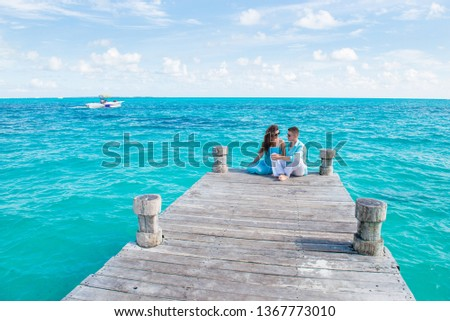 Young beautiful couple in blue and white clothes are sitting at the wooden pier. Drone view. Girl touch at the guy's head, and they are looking each other. Turquoise color water behind them. Vacation  #1367773010