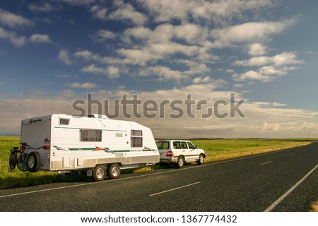 "WITTENOOM, AUSTRALIA - APR 26 2007: Caravan and SUV parked on roadside. Many retired Australians known as ""Grey Nomads"" enjoy touring and camping in similar rigs. #1367774432"