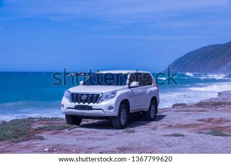 Caracas, Venezuela, 06.10.2018: a new armored Toyota Land Cruiser Prado along the wild sea coast. #1367799620