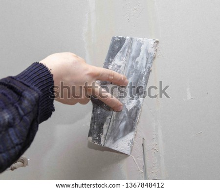 Worker aligns the walls with plaster. Repair in the house. #1367848412