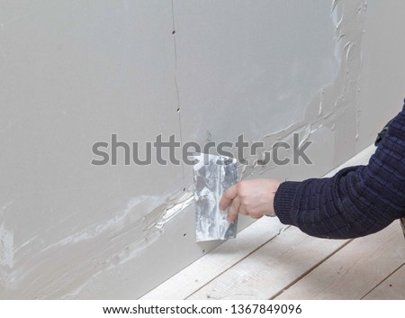 Worker aligns the walls with plaster. Repair in the house. #1367849096
