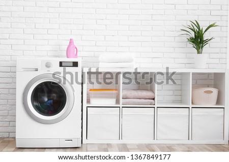 Modern washing machine near brick wall in laundry room interior #1367849177