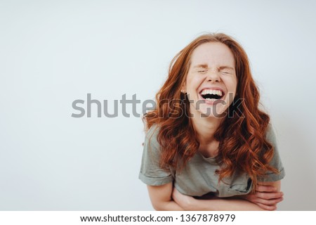 Young woman with a good sense of humor enjoying a laugh screwing up her eyes in amusement over white with copy space #1367878979