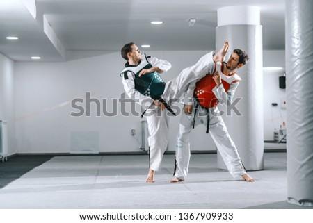 Two Caucasian sporty men sparring in tekwondo fittings barefoot. #1367909933