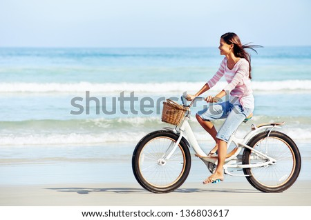 carefree woman with bicycle riding on beach sand having fun and smiling #136803617