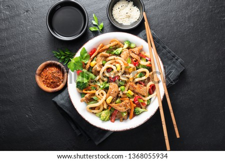 Udon stir fry noodles with pork meat and vegetables in a white plate on black stone background. #1368055934