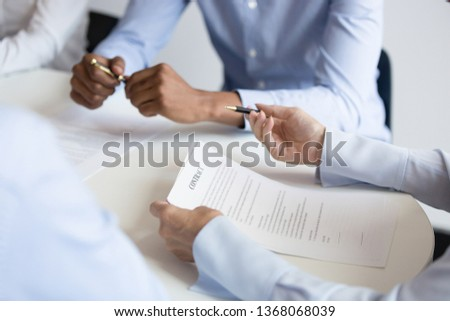 Business woman holding checking benefit reading legal paper form at group meeting, client customer negotiating on contract terms at table ready to make agreement sign document concept, close up view