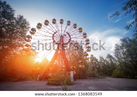 Ferris wheel on the main square of Pripyat. Abandoned attraction in a radioactive city. The street is overgrown with trees and bushes. #1368083549
