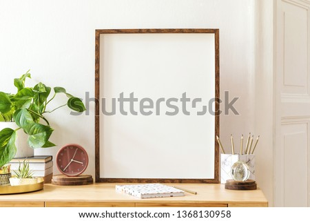 Modern scanidnavian interior with mock up photo frame, design office accessories and plants on the wooden desk. Beautiful mirror on the white wall. Creative desk of home decor. Warm and sunny room. #1368130958
