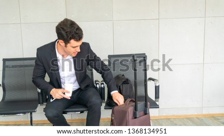 business man is sitting on chair waiting for business trip travel with suitcase #1368134951