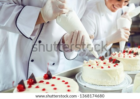 Two pastry chefs decorate a cake from a bag in a pastry shop #1368174680