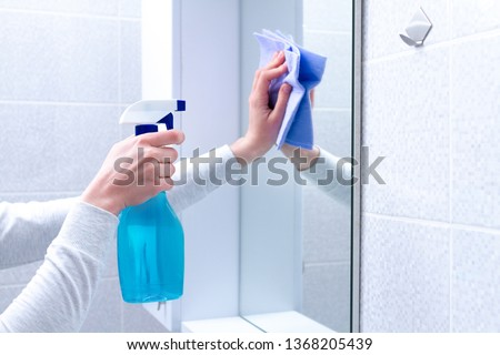Cleaning and polish mirror with rag and spray in bathroom at home. Housekeeping and cleaning service. Clean house, cleanliness #1368205439