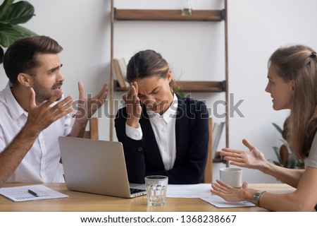 Stressed annoyed office employee manager having headache migraine at business meeting with complaining client customer tired of angry colleagues arguing shouting having conflict dispute at workplace #1368238667
