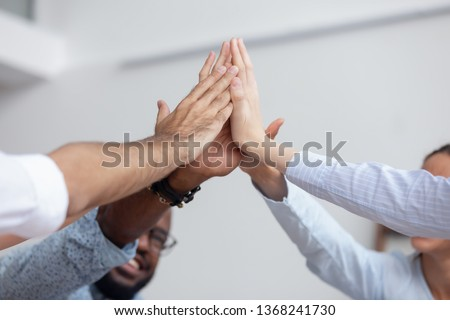 Multi ethnic corporate office business team winners join hands give high five together, success gesture, startup triumph, professional victory, teamwork accomplishment teambuilding concept, close up #1368241730