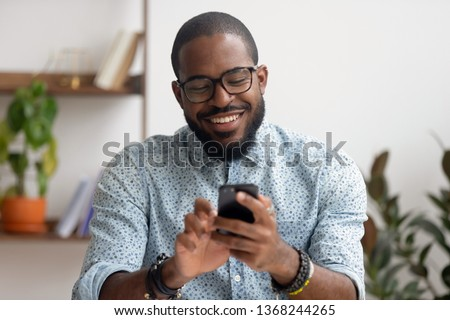 Happy african american businessman using phone mobile corporate apps at workplace texting sms, smiling black man looking at smartphone browsing internet, office technology and digital communication #1368244265