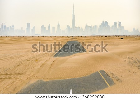 Stunning aerial view of a deserted road covered by sand dunes in the middle of the Dubai desert. Beautiful Dubai skyline surrounded by fog in the background. Dubai, United Arab Emirates. #1368252080