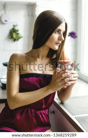 beautiful young girl in Burgundy pajamas in the kitchen #1368259289