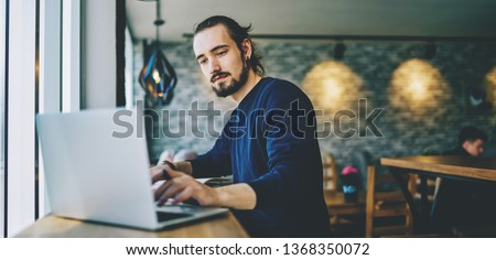Caucasian student watching webinar on laptop computer improving skills on programming, serious professional web designer working on freelance sitting in cafeteria and using good wifi connection Royalty-Free Stock Photo #1368350072