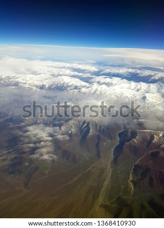 Flight altitude, view from the plane to the ground, unlimited landscape, beautiful nature, sky and city, mountains of Almaty, Kazakhstan #1368410930