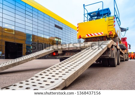 Trawl transport special machines. Loading of special equipment on the tow truck with the help of ladders. Aluminum ramps for vehicles. Trawl with aluminum ramps. Transportation of oversized cargo. #1368437156