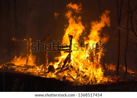 The fire wriggles over the burnt down building. A pile of coals on the site of a burnt house. Fire everywhere and smoke in the residential area at night against the backdrop of smoldering trees. #1368517454