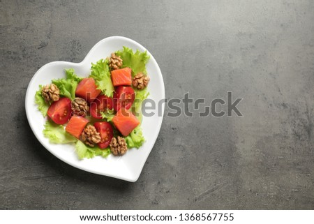 Plate of salad on grey background, top view with space for text. Heart-healthy diet #1368567755