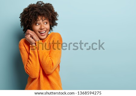 Happy pleased Afro American woman keeps hands together near face, focused away, notices desirable things, laughs, dressed in bright sweater, poses against blue background with free space aside #1368594275