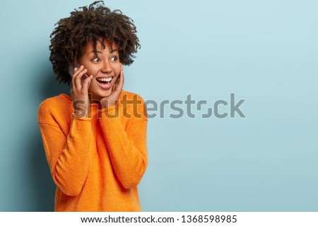 Emotional cheerful female talks on mobile phone, shares impressions with interlocutor, enjoys modern technologies, wears casual clothes, isolated over blue background, calls friend via cellular #1368598985