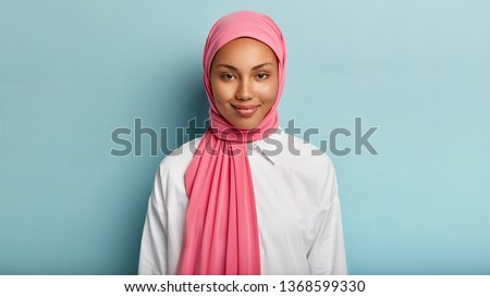 Headshot of lovely satisfied religious Muslim woman with gentle smile, dark healthy skin, wears pink scarf on head, white shirt, isolated over blue background, has no make up, natural beauty #1368599330