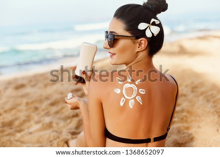 Sun shape created from sunscreen lotion on young woman's back. Skin protection.Skin and Body Care.Facial  treatment. Sun Cream Safety sunbathing concept. Copy space #1368652097
