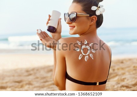 Woman Applying Sun Cream  on Tanned  Shoulder In Form Of The Sun. Sun Protection.Sun Cream. Skin and Body Care. Girl Using Sunscreen to Skin. Female Holding Suntan Lotion and Moisturizing Sunblock. #1368652109