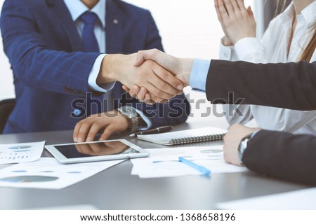 Business people shaking hands, finishing up a papers signing. Meeting, agreement and lawyer consulting concept #1368658196