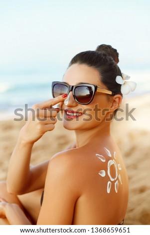 Suntan Lotion. Sexy Young Woman in Bikini  Applying Sunscreen Solar Cream.Sun Protection. Sun Cream. Skin and Body Care.Girl Holding Moisturizing Sunblock. Sun shape on the shoulder. Skin Protection #1368659651