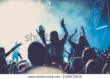 cheering crowd with raised hands at concert - music festival #1368670610