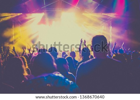 cheering crowd with raised hands at concert - music festival #1368670640