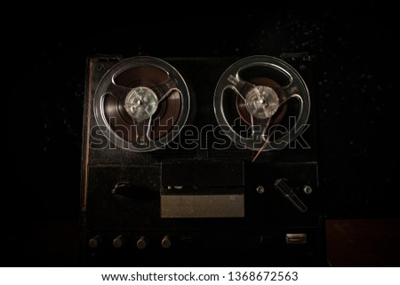 Old vintage reel to reel player and recorder on dark toned foggy background. Analog Stereo Open Reel Tape Deck Recorder Player with Reels. Selective focus #1368672563