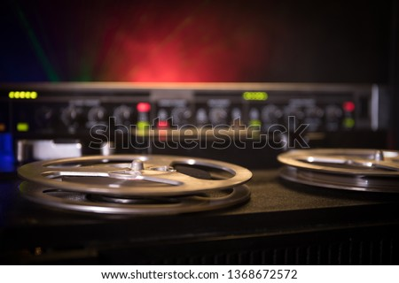 Old vintage reel to reel player and recorder on dark toned foggy background. Analog Stereo Open Reel Tape Deck Recorder Player with Reels. Selective focus #1368672572